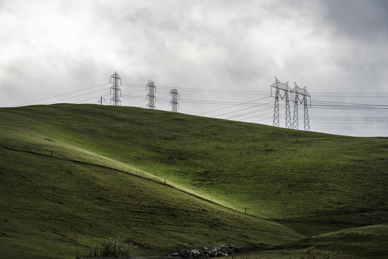Lush green hills frame rows of power lines west of Modesto in California's San Joaquin Valley